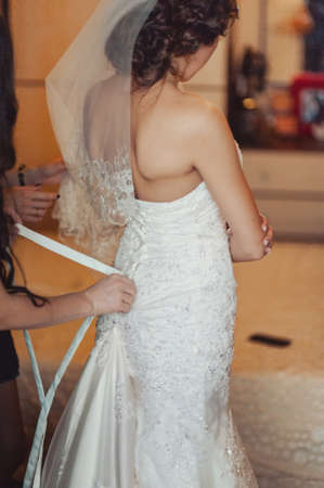 Fashionable bridesmaids dresses helped wear bow on back of wedding dress bride. Morning wedding day.