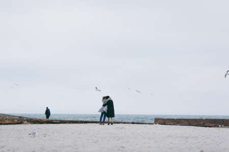 collisions: Girl wearing warm casual blue coat walking on the beach alone,Sea background,cold toned colors.lifestyle image,dreaming girl.walking alone,enjoy her time,sea-gull around,storm