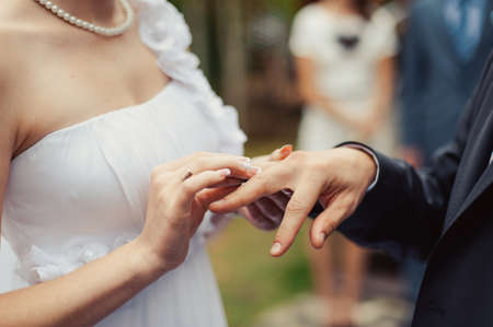fingers put together: Putting on rings. The bride and groom dress rings