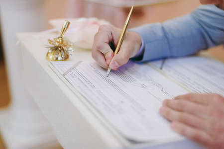 Signature Ceremony. The bride and groom sign the documents about the marriage Stock Photo