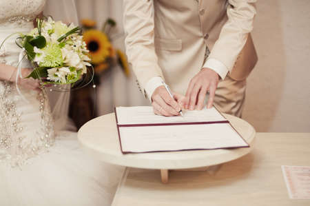 registro: Signature Ceremony. The bride and groom sign the documents about the marriage Foto de archivo