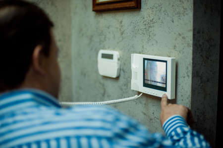 De man drukt op de knop van het intercompaneel