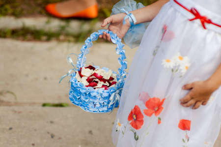 Little bridesmaid with a basket of rose petals Stock Photo