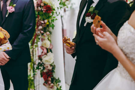 breaking: Closeup photo of bride and groom breaking traditional loaf