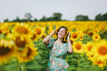 The girl attached sunflowers to her ears Stock Photo