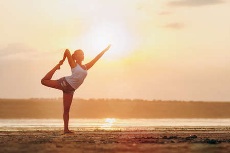 The pretty woman doing yoga at sunset outdoors