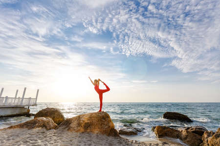 The woman in a red suit practicing yoga on stone at sunrise near the sea