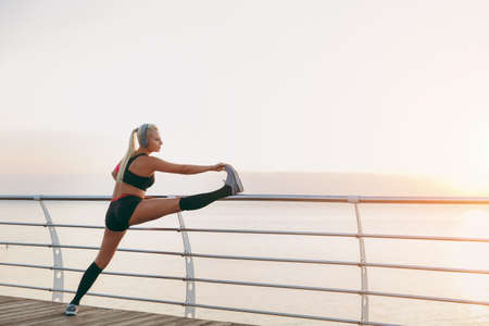 The young beautiful athletic girl with long blond hair in headphones listening to music and doing stretching at sunrise over the sea