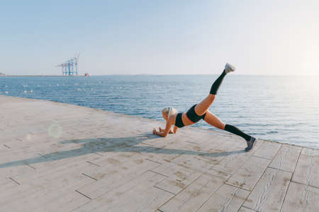 The young beautiful athletic girl with long blond hair in black clothes training and doing exercises, raising her leg up at sunrise over the sea