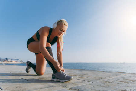 The young beautiful athletic girl with long blond hair in headphones, listening to music and lacing sneakers at dawn over the sea