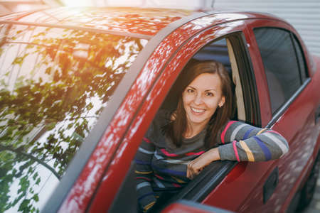 A beautiful young happy smiling European brown-haired woman with healthy clean skin dressed in a striped t-shirt sits in her red car with black interior. Traveling and driving concept. Stock Photo