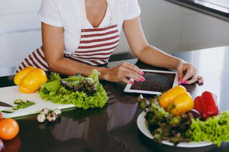 エプロンの若い幸せな女性は、台所でタブレットでレシピを見て。野菜 ...