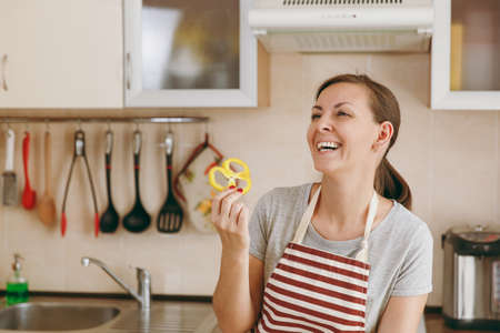 The young happy attractive woman in an apron holds yellow pepper in the kitchen. Dieting concept. Healthy lifestyle. Cooking at home. Prepare food. Banque d'images