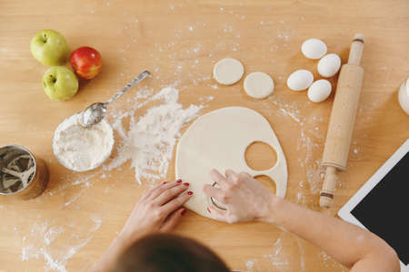 The young woman sitting at a table with flour and cut out a glass in a dough circles for dumplings in the kitchen. Cooking home. Prepare food. Top view.
