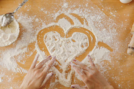 The hand drawn heart in flour on the kitchen table and other ingredients. Top view.
