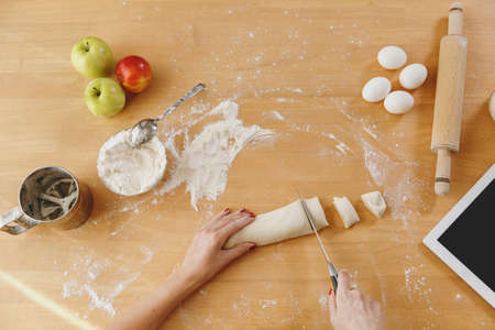 A young woman sitting at a table with tablet, cuts a dough with a knife into pieces at home in the kitchen. Cooking home. Prepare food. Top view. Stock Photo