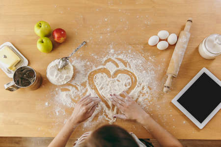 The hand drawn heart in flour on the kitchen table and other ingredients and tablet. Top view.