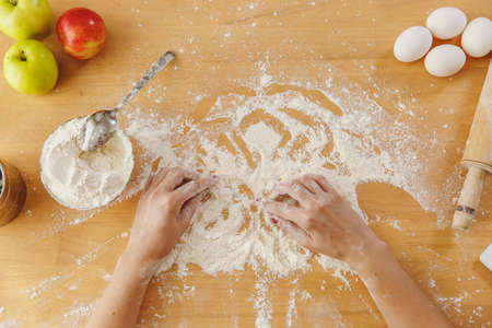 Top view of womens hands, flour and other ingredients on a kitchen table