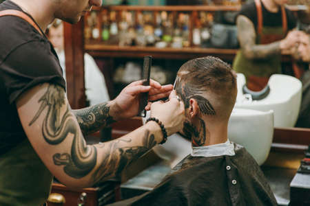 Close up shot of man getting trendy haircut at barber shop. The male hairstylist in tattoos serving client. Stock Photo