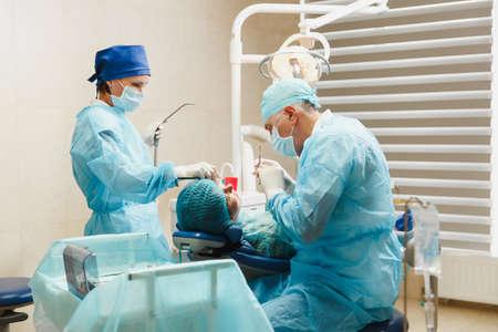 Männlicher alter Berufszahnarztchirurg in der Uniform und im weiblichen Assistenten hilft, Operation durchzuführen, Zahnimplantatzähne des Frauenpatienten im Kliniklichtbüro mit moderner Werkzeugausrüstung zu installieren