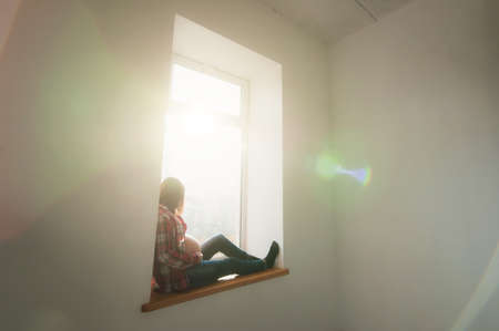 Happy pregnant young brunette woman with big belly sitting on window in sunlight room at home, tummy in sunny. Pregnancy, parenthood, family, motherhood, parents, children, people expectation concept