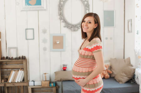 Happy pregnant young brunette woman in striped long dress with big belly in decor room, tummy, teddy bear. Pregnancy, parenthood, family, motherhood, parents, children, people and expectation concept