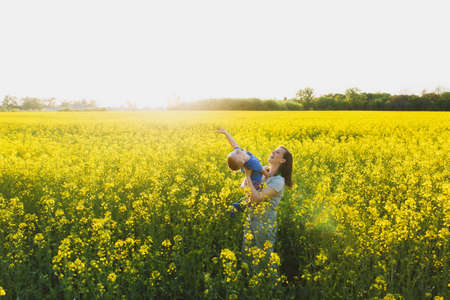 Joyful woman walk on green yellow flowering field background, rest, have fun, play, toss up little cute child baby boy. Mother, little kid son. Family day 15 of may, love, parents, children concept