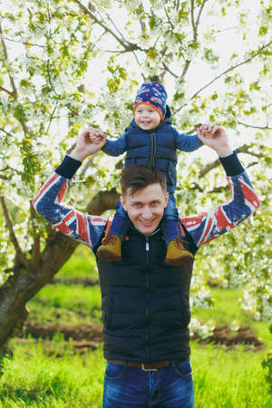 Smiling fun man rest on nature hug, play, kiss with little cute child baby boy. Father keeps on shoulders little kid son on white flower tree. Family day 15 of may, love, parents, children concept