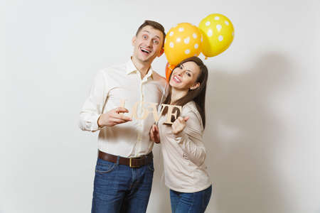Cute couple in love. Man, woman with wooden word Love, yellow, orange balloons isolated on white background. For advertisement. St. Valentines Day, International Womens Day birthday holiday concept