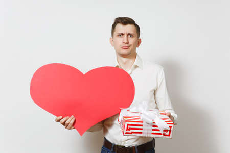 Dissatisfied man in shirt holding big red heart, present box with gift isolated on white background. Copy space for advertisement. St. Valentines Day, International Women Day birthday holiday concept