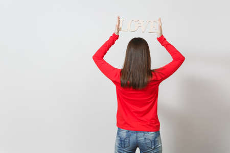 Young woman in red casual clothes turning back to camera, holding wooden word love above head on white background. Copy space for advertisement. St Valentines Day or International Women s Day concept
