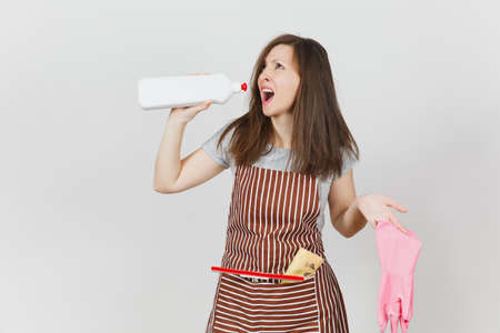Young fun crazy loony wild screaming housewife tousled hair, in apron squeegee cleaning rag in pocket isolated on white background. Mad woman drink bottle with cleaner liquid, pink gloves. Copy space Stock Photo