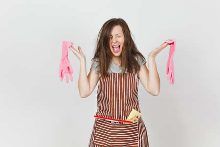 Young fun crazy dizzy loony wild screaming housewife tousled hair in striped apron squeegee cleaning rag in pocket isolated on white background. Mad woman and pink gloves Copy space for advertisement