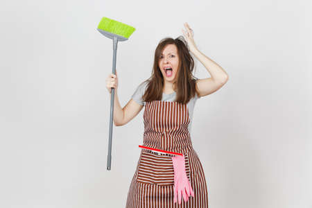 Young fun crazy dizzy loony wild screaming housewife tousled hair in striped apron squeegee pink gloves in pocket isolated on white background. Mad witch woman broom. Copy space for advertisement Stockfoto