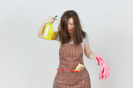 Young fun crazy loony wild screaming housewife tousled hair in apron squeegee rag in pocket isolated on white background. Mad woman shoot from spray bottle with cleaner liquid pink gloves. Copy space Stock Photo