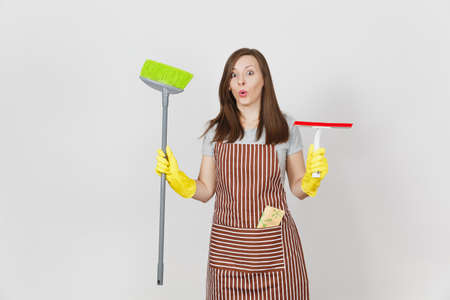 Young smiling housewife in striped apron, yellow gloves isolated on white background. Housekeeper woman cleaning maid holding, sweeping broom, squeegee. Copy space for advertisement. Advertising area