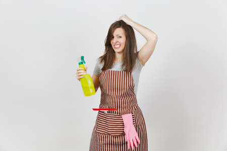 Young fun crazy dizzy loony wild housewife tousled hair striped apron squeegee cleaning rag in pocket isolated on white background. Mad woman spray bottle with cleaner liquid pink gloves. Copy space Stock Photo