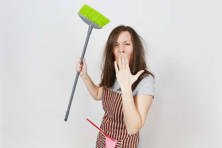 Young fun crazy dizzy loony wild screaming housewife tousled hair in striped apron isolated on white background. Mad witch woman with broom, shut up, cover mouth by hand. Copy space for advertisement