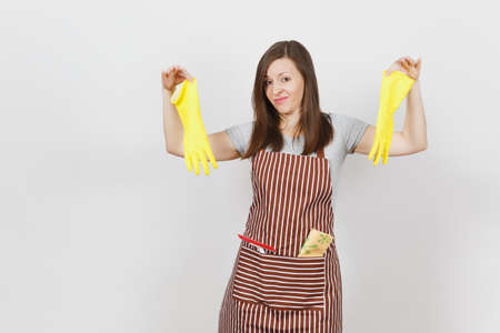 Young sad upset tired shocked housewife in striped apron with cleaning rag in pocket isolated on white background. Housekeeper woman holds smell yellow gloves in spreading hands. For advertisement