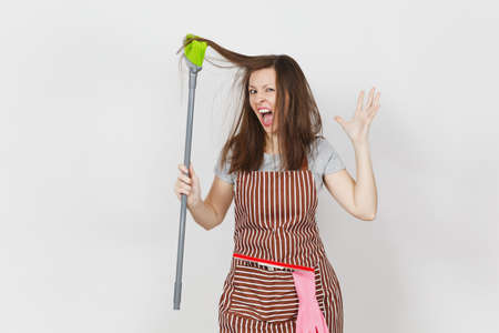 Young fun crazy dizzy loony wild aggressive housewife tousled hair in striped apron in pocket isolated on white background. Mad woman comb out tousled brown hair broom. Copy space for advertisement Stock Photo