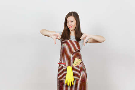 Young sad upset tired crying housewife in striped apron with cleaning rag, squeegee, yellow gloves isolated on white background. Beautiful housekeeper woman showing thumbs down. For advertisement