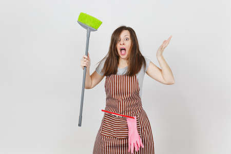 Young fun crazy dizzy loony wild screaming housewife tousled hair in striped apron squeegee pink gloves in pocket isolated on white background. Mad witch woman broom. Copy space for advertisement Stock Photo
