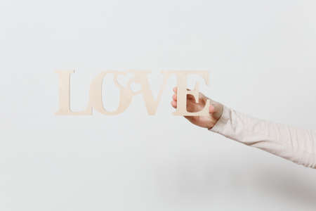 Close up woman holding wooden light word Love in hand isolated on white background. Copy space for advertisement. With place for text. St. Valentine's Day or International Women's Day concept