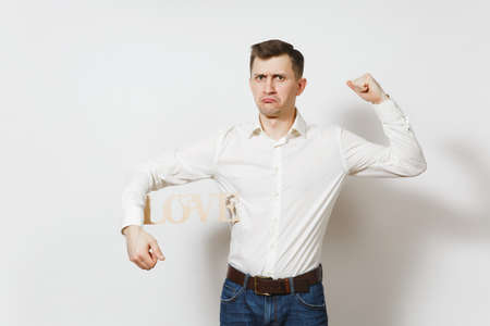 Young confused sad upset man in shirt holding wooden word Love isolated on white background. Copy space for advertisement. St. Valentines Day, International Womens Day, birthday, holiday concept Stock Photo