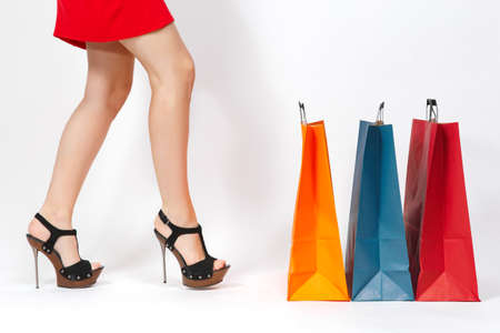 Slender long female legs in black sandals, caucasian woman in red dress kicking multi colored packets with purchases after shopping isolated on white background. Copy space for advertisement