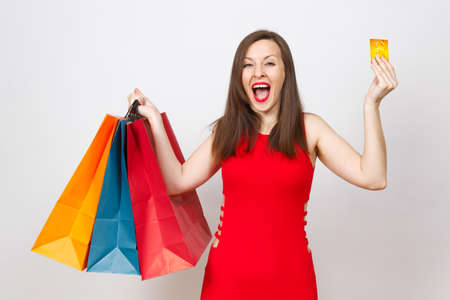 Pretty impressive fashionable young brown-hair woman in red dress holding credit card, multi colored packets with purchases after shopping isolated on white background. Copy space for advertisement Reklamní fotografie