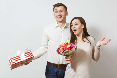 Young couple in love. Man and woman with bouquet of beautiful roses flowers, present box with gift isolated on white background. St. Valentines Day, International Womens Day birthday holiday concept