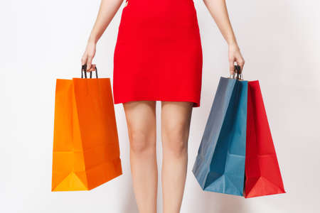 Slender long female legs, European caucasian woman in red dress holding three multi colored packets with purchases after shopping isolated on white background. Copy space for advertisement
