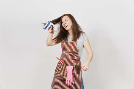 Young fun crazy dizzy loony wild housewife in striped apron with squeegee, pink gloves in pocket isolated on white background. Mad woman comb out tousled brown hair by brush for cleaning. Copy space