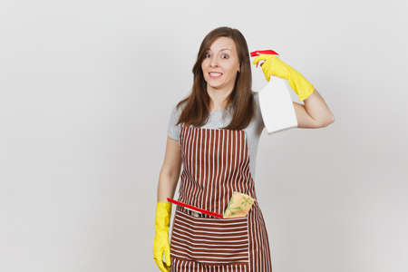 Young fun housewife in yellow gloves, striped apron, cleaning rag, squeegee in pocket isolated on white background. Housekeeper woman shoots from spray bottle with cleaner liquid. Bottle copy space Stock Photo